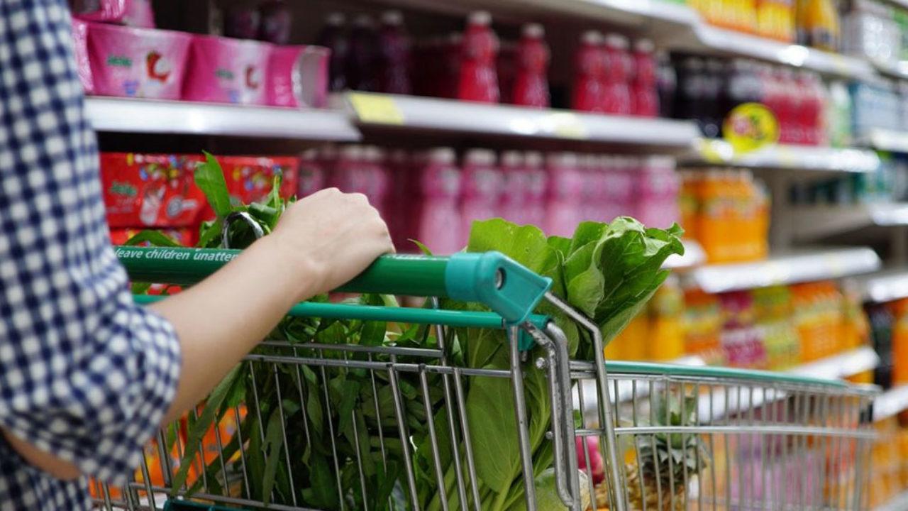 Una mujer empujando un carro de supermercado