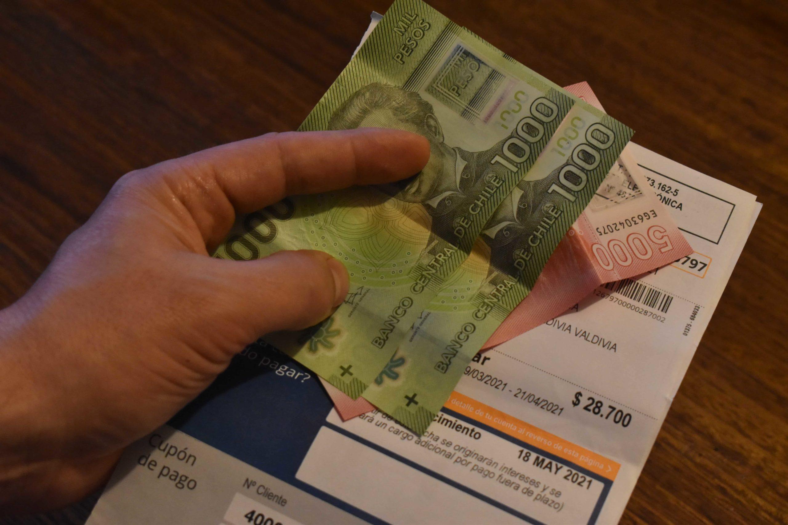 La mano de una persona sosteniendo boletas de servicios básicos y dinero en efectivo